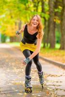 lachendes Mädchen Rollschuhlaufen im Herbstpark eins