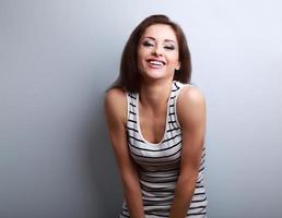 glückliche lachende junge Frau der natürlichen Emotion, die auf Blau schaut foto