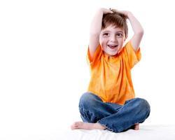 echte Menschen: lachender kaukasischer kleiner Junge, der in voller Länge sitzt foto
