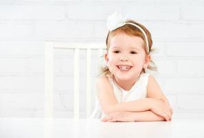 fröhliches lustiges lustiges Mädchenkind, das am leeren weißen Tisch lacht foto