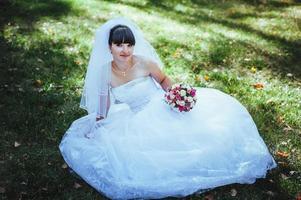 schöne Braut, die in ihrem Hochzeitstag aufwirft foto
