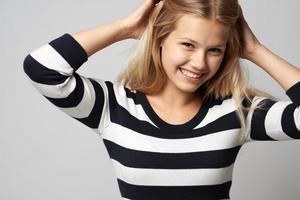 schönes Mädchen in einem gestreiften Pullover süß lächelnd foto
