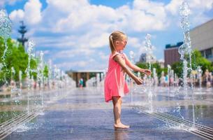 entzückendes kleines Mädchen, das im Straßenbrunnen spielt foto