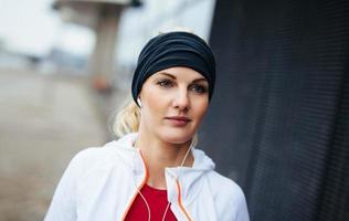 Fitnessfrau, die im Freien entspannt schaut