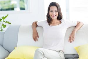 lächelnde schöne Brünette, die sich auf der Couch entspannt