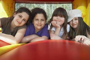 glückliche Mädchen, die in Hüpfburg entspannen foto