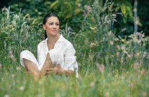 junge entspannende Frau, die auf dem Gras sitzt foto