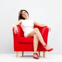 schönes lächelndes Mädchen entspannte sich auf rotem Sessel foto