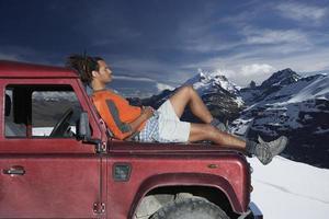 Mann, der auf Motorhaube gegen Berge entspannt foto