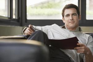 entspannter Geschäftsmann, der auf Sofa mit Ordner sitzt foto