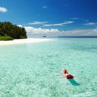 Frau, die auf aufblasbarer Matratze im Meer entspannt