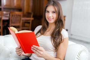 Frau liest ein Buch, während sie sich auf der Couch entspannt foto