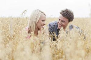 glücklicher Mann, der Frau beim Entspannen inmitten des Feldes betrachtet foto