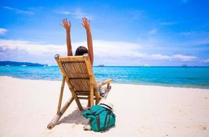 junge Frau, die im hölzernen Stuhlstrand im tropischen Urlaub entspannt foto