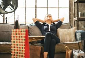 entspannte junge Frau mit Einkaufstüten, die in der Dachbodenwohnung sitzen foto