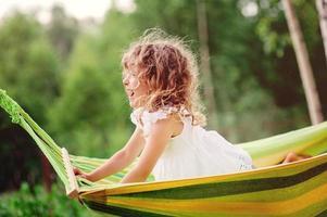 glückliches Kindermädchen, das in der Hängematte im Sommergarten entspannt