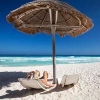 Frau entspannt am karibischen Strand mit Sonnenschirmen und Betten