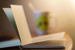 entspannendes offenes Buch mit unscharfer Tasse Tee im Hintergrund