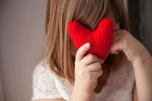 Mädchen versteckt sich hinter einem gestrickten roten Herzen, Valentinstag,
