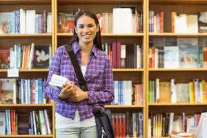 lächelnder Universitätsstudent, der Lehrbuch hält