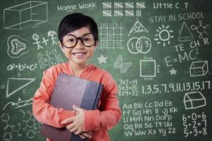 süßes kleines Mädchen hält Lehrbuch in der Klasse