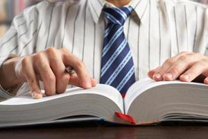Geschäftsmann und / oder Professor, der ein Lehrbuch liest foto