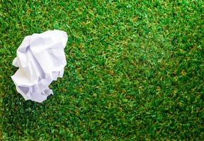 zerknittertes Papier auf grünem Grashintergrund foto