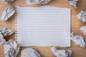 weißes Notizbuch mit Bleistift und zerknittertem Papier