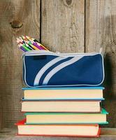Bücher und Schulgeräte auf einem Holzregal.
