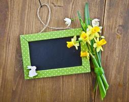 kleine Tafel und Frühlingsblumen foto
