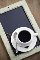 Tasse Kaffee auf schwarzer Tafel, Draufsicht, vertikal foto