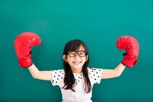 glückliches kleines Mädchen mit roten Boxhandschuhen vor Tafel foto