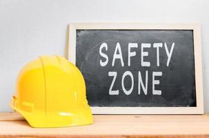 Helmsicherheit mit Tafel (Sicherheitszone) auf dem Tisch foto
