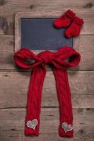 Kreidetafel mit rot gestrickter Socke und Schleife auf Holz foto