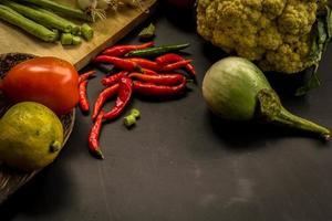 Gemüse auf schwarzem Tafelhintergrundraum. Karotten, Tomaten, foto