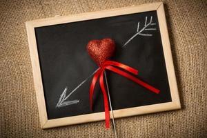 gezeichnet auf Tafelpfeil, der durch dekoratives Herz geht foto