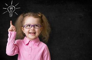 Kind in Gläsern mit Ideenlampe auf Schultafel