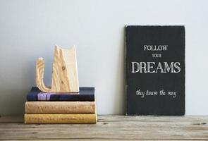Motivationszitat Folgen Sie Ihren Träumen an der Tafel mit Büchern