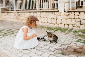 kleines Mädchen, das mit Katze im Freien spielt foto