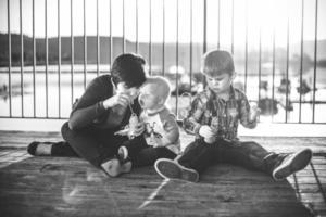 Mutter und Jungen blasen Blasen auf dem Deck am Wasser foto