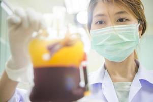 asiatische Wissenschaftlerin arbeitet mit Gerät für die Blutanalyse foto