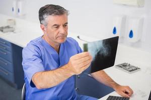 Zahnarzt, der aufmerksam Röntgen studiert foto