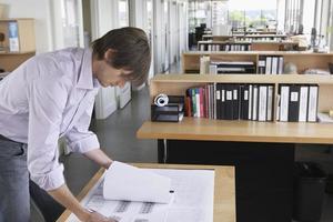 Mann, der Blaupause im Büro studiert foto
