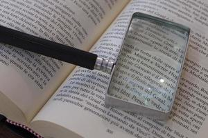 Lupe auf einem offenen Buch foto