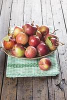 Korb mit Äpfeln auf einem Holztisch foto