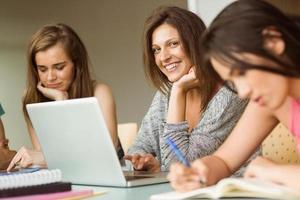 lächelnde Freunde sitzen studieren und benutzen Laptop