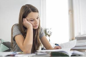 gelangweiltes Mädchen, das am Tisch im Haus studiert foto