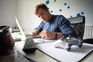 Teenager, der im Schlafzimmer mit Laptop studiert foto