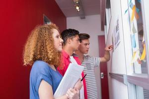 ernsthafte Studenten, die mit Grafiken an der Wand lernen foto