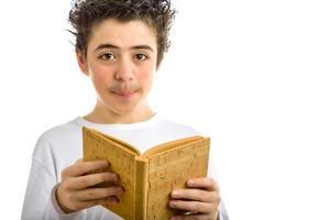 süßer Junge liest braunes Kork leeres Buch lächelnd foto
